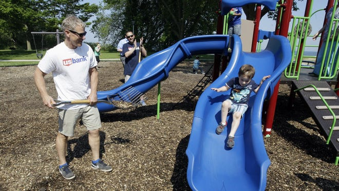 Mike Nickels, left, watches as a youngster tests out the new piece of playground equipment Thursday at King Park in Sheboygan. US Bank partnered with the Sheboygan Neighborhood Pride and the City of Sheboygan. The US Bank foundation donated $24,000 for the project.