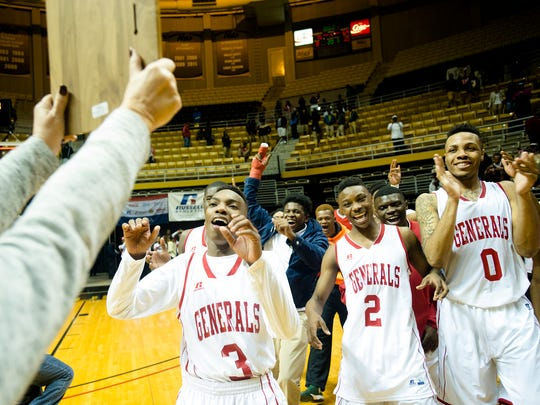 Lee's Roderic Scott (3), Henry Ruggs (2) and Trenton Clayton (0) go to receive the regional trophy after Lee won the the Class 7A Central Region Championship. In the background celebrating is Shaquille Johnson who was shot and killed in Montgomery on Feb. 4, 2017.