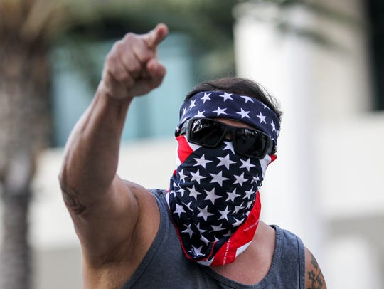 A demonstrator masked with a U.S. flag protests outside