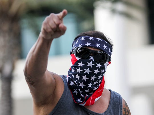 A demonstrator masked with a U.S. flag protests outside of California Republican Convention in Anaheim, Calf., on Friday, Oct. 20, 2017.