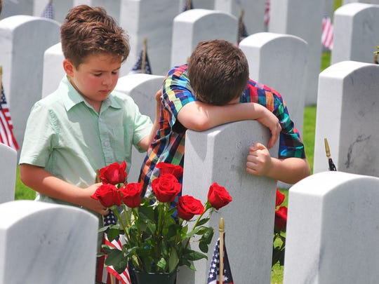 A large crowd attended the Memorial Day Observance at the Canaveral National Cemetery in Mims  on Monday. Nicolas Amador comforts his brother Marcelo at their grandfather - Hector Zapata's - grave. They were their with their parents, who are from Lake Mary.