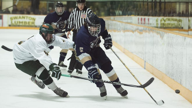 BFA's Owen Ladd (6) battles for the puck with Essex's Johan Janaro (5) during the boys hockey game between the Essex Hornets and the BFA St. Albans Bobwhites earlier this season.