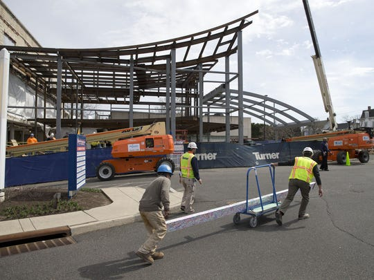 Workers carry an autographed beam for Riverview Medical Center's new cancer center in Red Bank.