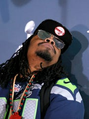 Seahawks' Marshawn Lynch looks toward the ceiling during a news conference for NFL Super Bowl XLIX, Jan. 28, 2015, in Phoenix.