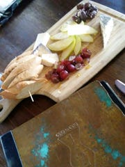 1.2.1. Tapas' fruit and cheese plate had a spear of lightly toasted crostini rounds, apple and grape slices drizzled with honey, garlicy herb marinated olives and three types of cheese.