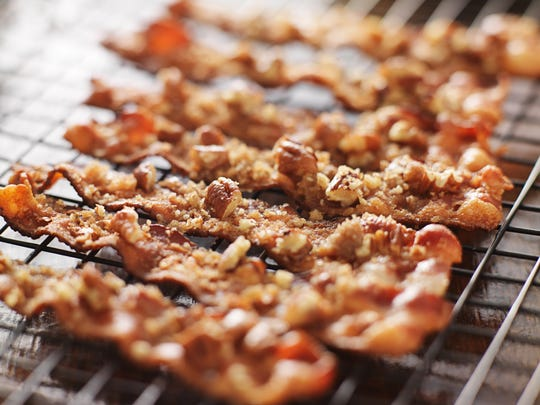 Candied bacon with pecans and brown sugar cooling on baking rack.