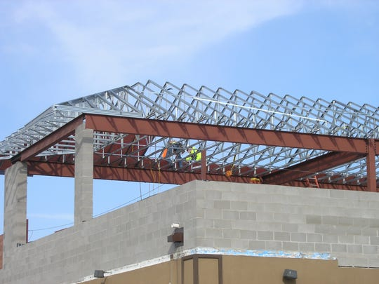 Crews work on the addition of a rooftop patio at Anduzzi's Sports Club in Ashwaubenon.