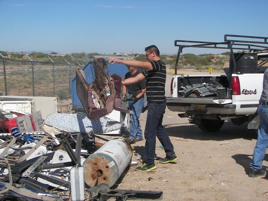 Residents unload trash onto a pile of scrap metal items at the Anthony Collection Center, 2120 E. O'Hara Road.