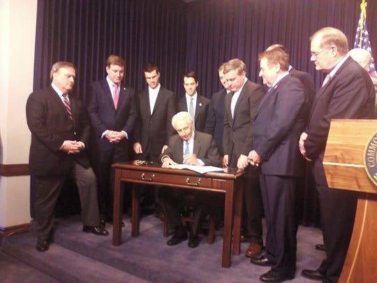 Gov. Steve Beshear signs the heroin bill into law at the Kentucky Capitol.