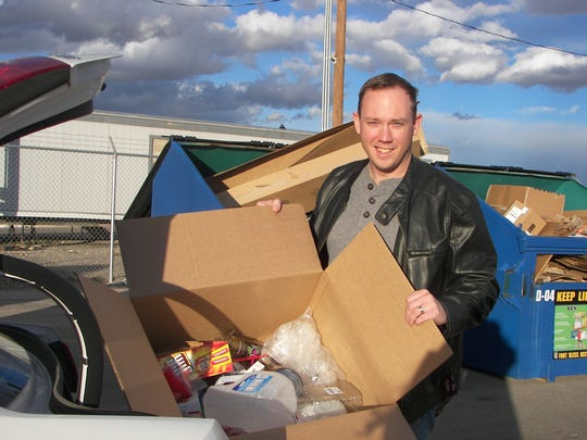 Josh Walters unloads a box of recyclables, including paper and plastic materials, from his vehicle. There is never a charge to dispose of recyclables, and there is a school recycling dumpster or a Recycling Center near you.