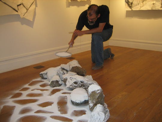 Artist Eric Kniss sifts kaolin to create his clay dust sculpture at the Staunton Augusta Art Center gallery in the Smith Center.