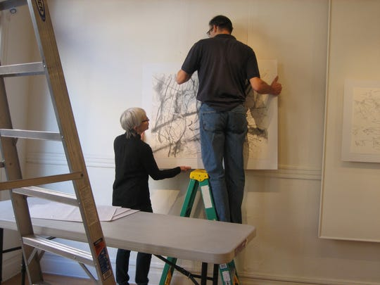 Eric Kniss hangs one of his drawings at the Staunton Augusta Art Center gallery in the Smith Center.