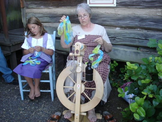 Children learn the basics of spinning wool at the