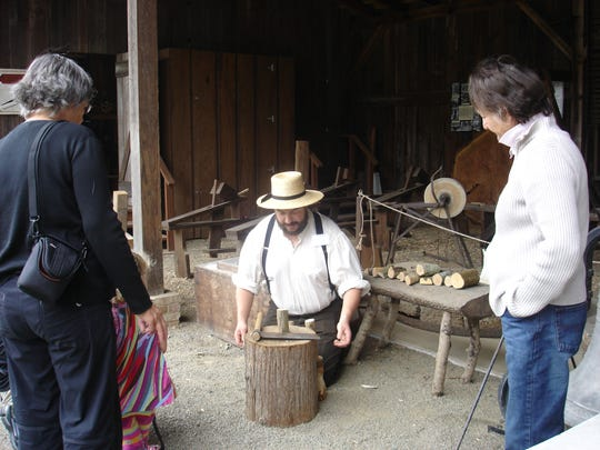 A volunteer shows visitors what life was like during pioneer days at Photo courtesy of Old Aurora Colony Historical Museum.