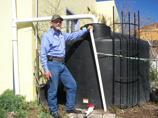 Ag agent Jeff Anderson stands beside the rainwater harvesting holding tank in his backyard. The huge tank can house up to 1,500 gallons of rainwater.