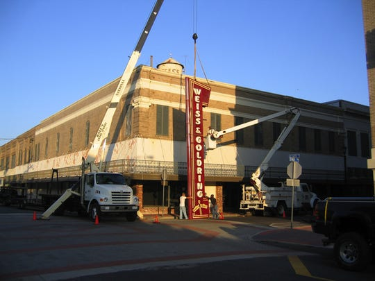 "This photo from July 2007 shows the sign from the former Weiss & Goldring building on Third Street in Alexandria being removed so that it could be relocated to the store's new location by the Alexandria Mall. The vacant building is being donated to the city of Alexandria, and Mayor Jacques Roy says that  opens up ""tremendous opportunities"" for re-use of the building, possibly in a public-private partnership."