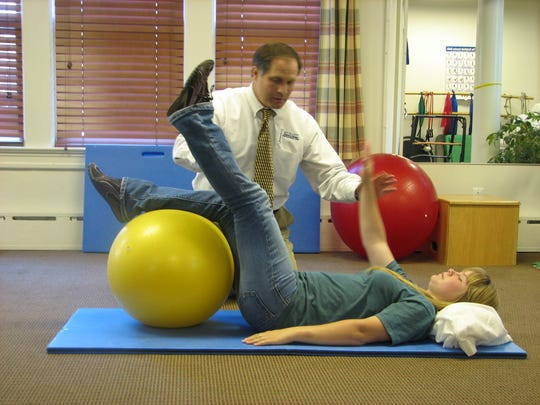 Stretches with a ball are among the many strengthening activities employed at Excellent Physical Therapy in Bedminster.