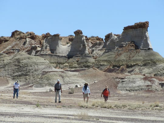 "Encore instructor Linda Wheelbarger, far right, leads students Elliott Hebert, Ken Russell and Charlotte Hebert through Hunter Wash amid towering hoodoos and eroded sandstone formations in the Bisti/De-Na-Zin Wilderness during last year's ""Using GPS Technology and Maps to Explore the Bisti"" class."
