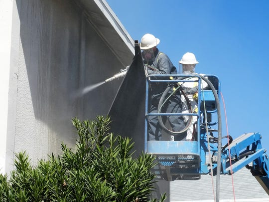 A clean blast crew works on the side of a building.