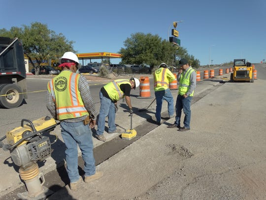 A road construction crew mechanically tamps down the