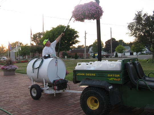 Clyde in Bloom volunteer Al Hench waters planters in downtown.