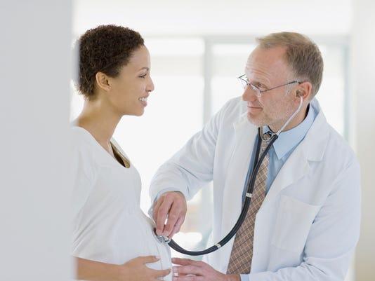 Doctor giving pregnant woman check-up
