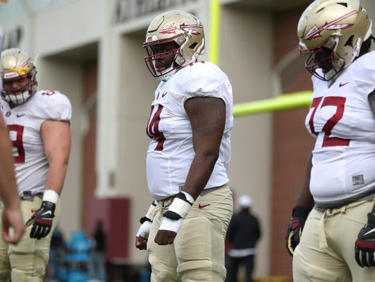 FSU's Derrick Kelly II, center, works with his lineman