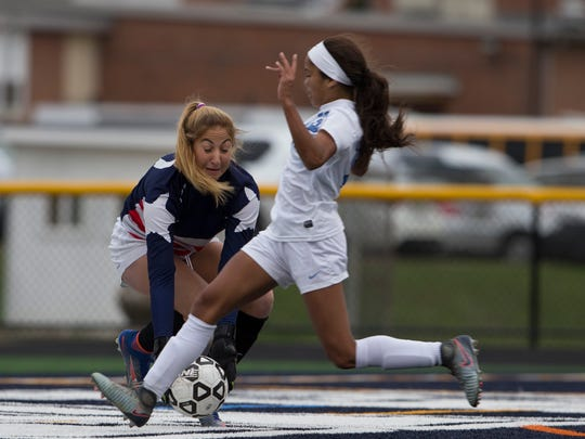 Freehold's Jada Colbert just misses a shot on goal as East Brunswick's Lauren Krinsky manages to scoop up the ball during closing minutes of regulation play. Freehold Township Girlsl Soccer defeats East Brunswick 2-1 in overtime for Central Jersey Group IV final in Howell NJ on November 9, 2017.