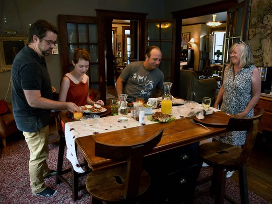 Doug McDaniel, left, serves breakfast to Laura Webb and Michael Benton. Faith McDaniel, right, prepared the eggs benedict for the guests of the bed and breakfast the McDaniels operate in the Fourth and Gill neighborhood Wednesday August 3, 2016. Knoxville is considering how to regulate Airbnb properties and other short-term rentals.