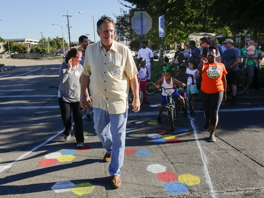 Mayor-President Joel Robideauxleads the first crossing of West Congress during the Complete Street Congress Block Party!, to celebrate the completion of new painting of traffic and bike lanes and crosswalks near the main library in Lafayette Oct. 8, 2016.