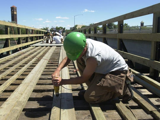 Members of the Montana Conservation Corps install Epoch decking, a composite wood and plastic material that doesn't require treatment, on the Weissman Trail Bridge.