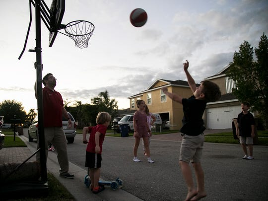 Ethan Kain, 8, shoots a basket while playing with his siblings in front of their house in Lehigh Acres recently. His dad Mike, left, is happy to be able to be a little more active with the kids since his kidney transplant in September.
