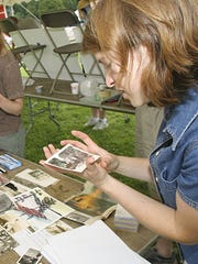 Carina Driscoll (right) looks through pictures of the area surrounding Oakledge Park from the late 1800s and early1900,