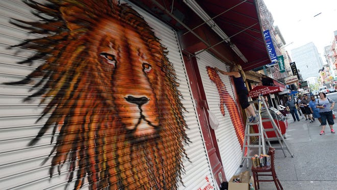 Artist J. Morello, after completing a painting of Cecil the Lion, works on another painting on a store front Aug. 6, 2015, in New York.