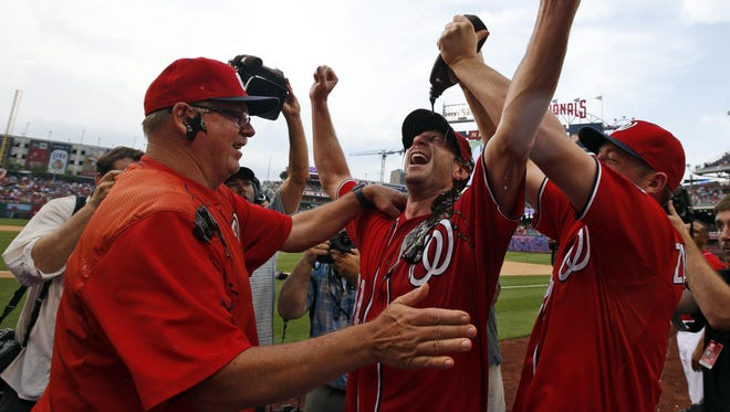 Jordan Zimmermann, right, douses Max Scherzer with chocolate syrup as Scherzer celebrates his feat with pitching coach Steve McCatty, left.