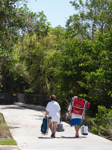 Beachgoers walk with their belongings to the Vanderbilt Beach Parking Garage at the beach access point in Naples, Florida on Saturday, Sept. 10, 2016. As more people come to Southwest Florida, debate is growing as to whether theyÕre being funneled into too few beach access points, with too limited and expensive parking.