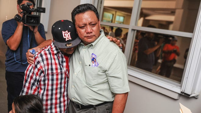 Roland Sondia hugs his son, Sean Paul Sondia, 25, after a press conference outside the Cathedral Pastoral Center in Hagåtña on Wednesday, June 15.  The elder Sondia went public at the press conference with allegations of sexual abuse, by then-Father Anthony Apuron in the 1970s. The alleged molestation took place when he was a 15-years-old altar boy at the Catholic church in Agat, Roland Sondia said.