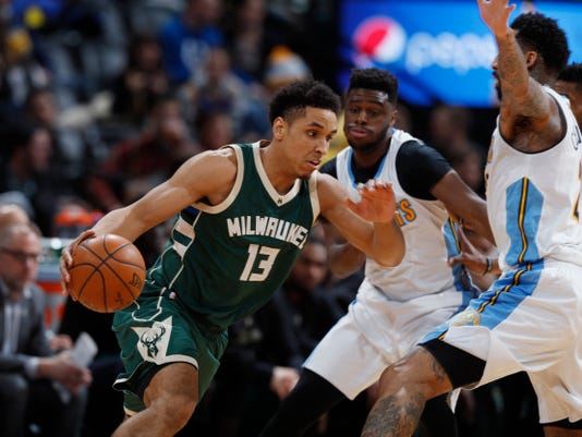 Milwaukee Bucks guard Malcolm Brogdon, left, drives to the net past Denver Nuggets guard Emmanuel Mudiay, center, and forward Wilson Chandler in the first half of an NBA basketball game Friday, Feb. 3, 2017, in Denver. (AP Photo/David Zalubowski)