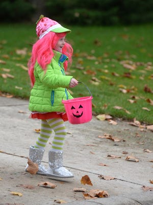 Kayla Johnson carries her matching pumpkin bucket while trick-or-treating on Halloween 2014.