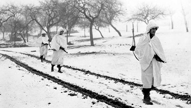 Three members of an American patrol cross a snow covered Luxembourg field on a scouting mission. White bedsheets camouflage them in the snow. Left to right: Sgt. James Storey, Newman, Ga.; Pvt. Frank A. Fox, Wilmington, Del., and Cpl. Dennis Lavanoha, Harrisville, N.Y. (30 Dec 1944). Lellig, Luxembourg   Signal Corps Photo #ETO-HQ-45-5003 (Hustead)