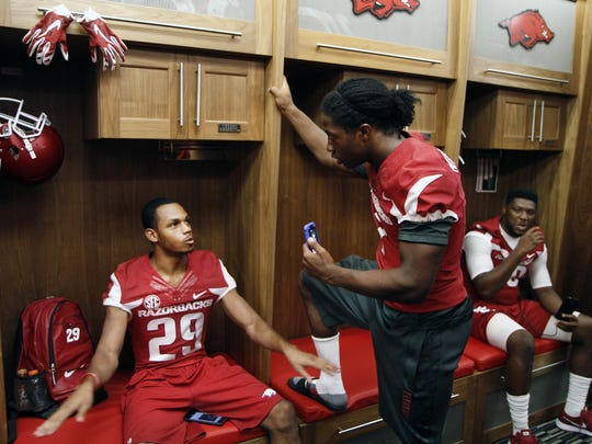 Arkansas' Damon Mitchell, center, mimics members of the media and interviews Jared Collins, left, in the players' locker room during the team's annual media day event.