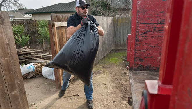 Mike Tyler, owner of Be Junk Free, removes unwanted materials from a Visalia home on Tuesday, January 2, 2018. The customer said his place looks better every time Tyler comes by.