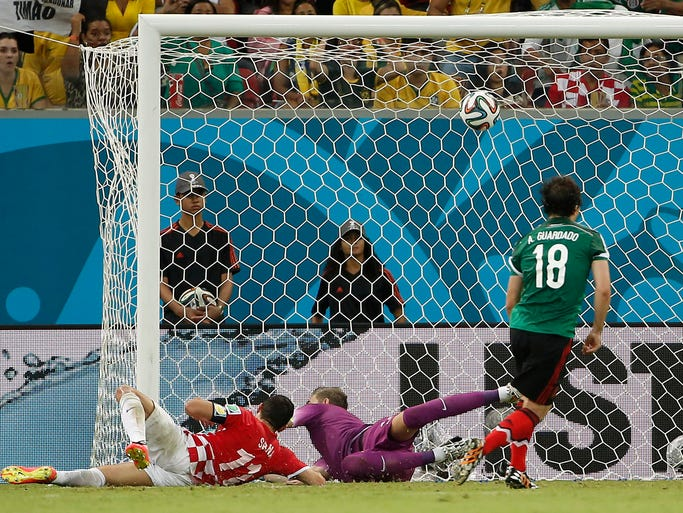 Jun 23, 2014; Recife, Pernambuco, BRAZIL; Mexico midfielder Andres Guardado (18) watches his shot go in for a goal past Croatia goalkeeper Stipe Pletikosa (1) and defender Darijo Srna (11) during the second half of Mexico's 3-1 win in a 2014 World Cup game at Arena Pernambuco. Mandatory Credit: Winslow Townson-USA TODAY Sports