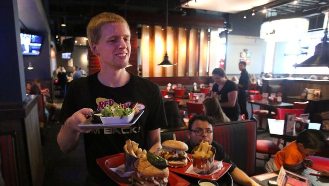 Tyler Keck, a server at Red Robin, serves lunch at the new location at Lancaster Mall during a test run on Friday. The new location, which opens officially on Monday, is 3,200 square feet larger than the former location across the mall on Center Street and seats 268 people.