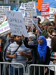 "A woman holds a sign that reads ""My Sharia Knows No"