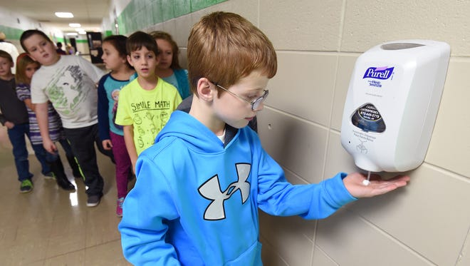 Yellville-Summit second grade student Layton Swafford grabs some hand sanitizer Monday while classmates wait in line. With area schools back in session and flu season in full swing, health care workers are emphasizing the importance of hand washing and sanitizing.