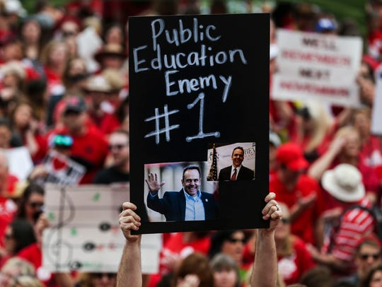 Thousands of teachers held signs during an April protest of possible budget cuts for education as well as pension reform.