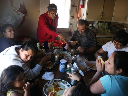 Cesar Chavez, center, enjoys a meal with his family at their home in Marshalltown on March 7. Chavez says he's behind on rent and utilities.