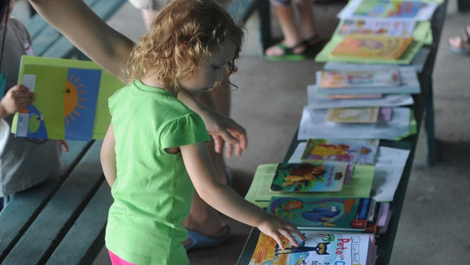 Alexandra Cooper picks up a book to take home at a Birth-to-Five Book Buddies event.