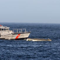 A surfer paddles out close to a capsized boat close near the Manasquan Inlet around 2:30 p.m. in Manasquan Friday.